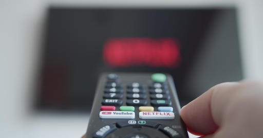 Pressing Netflix dedicated button on a remote control on smart TV - streaming service concept Live Action