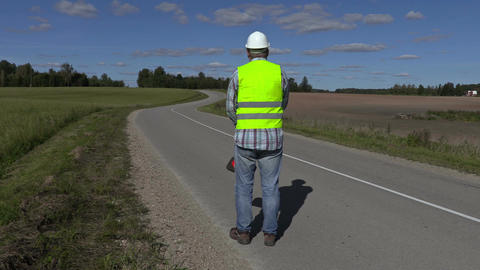 Road construction worker with traffic cone on the road Footage
