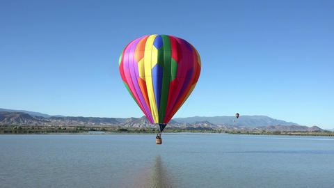 Hot air balloon skips across mountain valley lake 4K 064 Footage