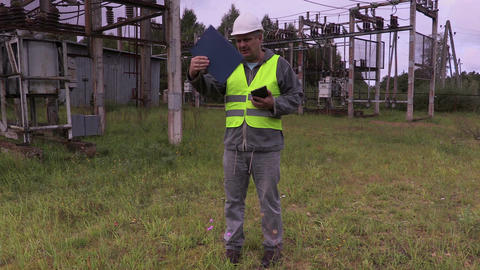 Electrician engineer gives the task to cut the grass in substation Live Action
