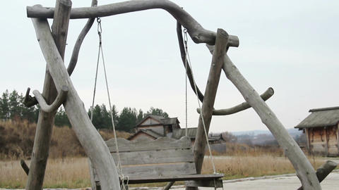 Old wooden swing hanging on ropes at open-air history and folklife museum Footage