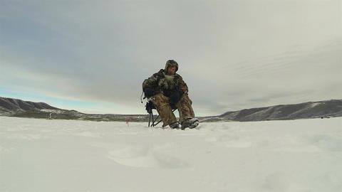 Ice fishing frozen lake man picks up pole HD 0228 Footage