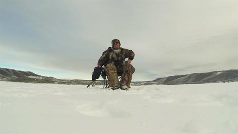 Ice fishing frozen lake sitting by hole HD 0228 Footage