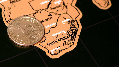 Person erase South Africa with one dollar coin on black scratch travel map ライブ動画