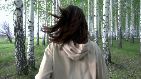 A young woman runs through a birch forest in slow motion. The girl runs between ライブ動画