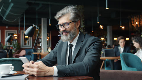Handsome mature man in suit using smart phone texting in restaurant alone Live Action