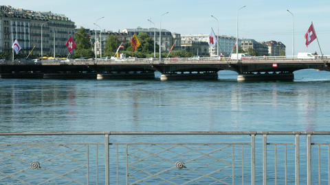 Mont-Blanc bridge with flags of red crescent, Switzerland, Geneva and red cross floating over Leman Live Action