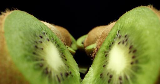 Juicy fresh kiwi fruit cut in half super macro shoot fly over 4k shoot on dark background Live Action