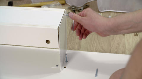 Hands screwing hexagon screw in white plank Live Action