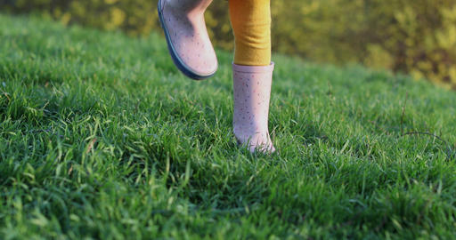 Children's legs stomp in pink rubber boots on green grass Live Action