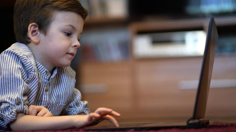baby boy in blue shirt watching on tablet GIF