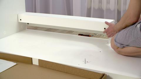 Handyman screwing hexagon screw in white plank Live Action