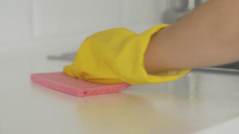 Housewife woman in yellow gloves clean the table with pink rag Live Action