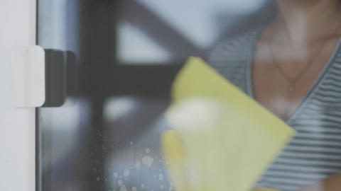Young woman in yellow gloves wash window with yellow rag and detergent Live Action