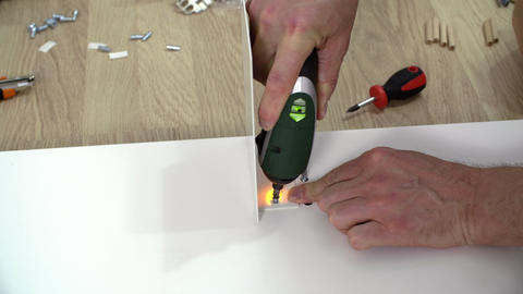 Male hands using electric screwdriver Live Action
