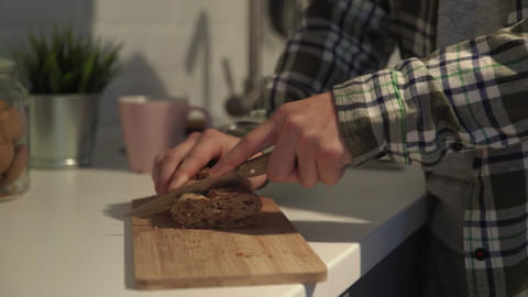 Close-up of slicing brown bread on cutting board. Man cuts dark bread with seeds Live Action