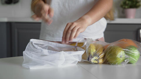 Close up of young woman move fruits from plastic bag to reusable mesh bag on the Live Action