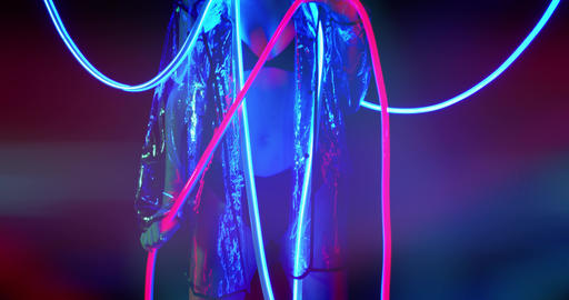 Sexy young woman is standing in neon light, holding the neon stripes, 4k Live Action