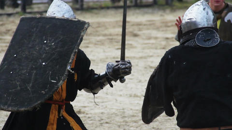 Two knights and referee on battle field, martial skills tournament reenactment Footage