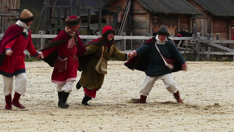 Medieval performance. Cheerful actors are dancing and jumping on the square Footage
