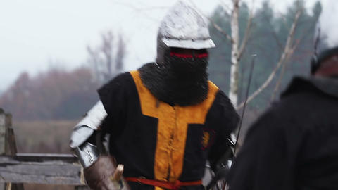 Two strong knights in steel armour fighting fiercely with swords on battle field Live Action