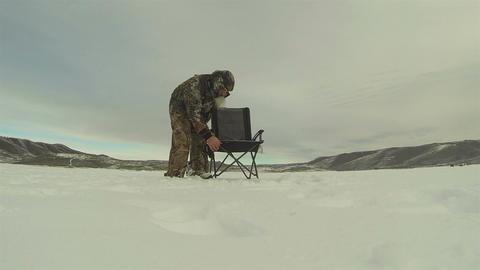 Man ice fishing frozen lake HD 0228 Footage