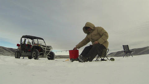Man ice fishing frozen lake winter mountains HD 0229 Footage