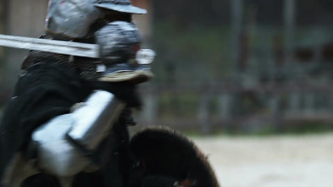 Two strong men in medieval armour reenacting duel between courageous knights Footage