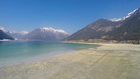 Low water level in lake for energy saving during off-season at Alpine ski resort Footage