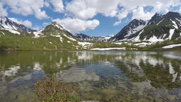 Mountains, mountain lake and clouds drifting across sky on sunny day Footage