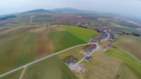 Aerial shot of green pasture, cultivated fields, farms and cottages. Agriculture Footage