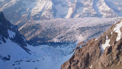 Magnificent horizontal pan of snowy mountain range, trees in beautiful valley Footage