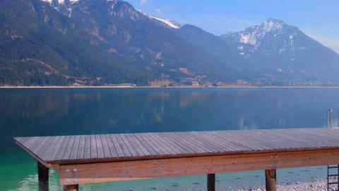 Horizontal pan of wooden pier near beautiful lake, mountains covered with snow Footage
