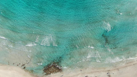 Drone view of little people on sandy beach with foamy waves rolling in. Top view Live Action