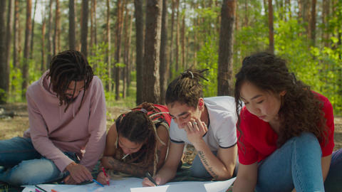 Diverse students making ecological project outdoors Live Action