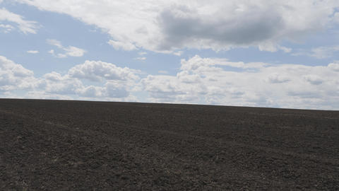 Field stretching into the sky. The field is ready for planting grain. Clouds floating across the Live Action