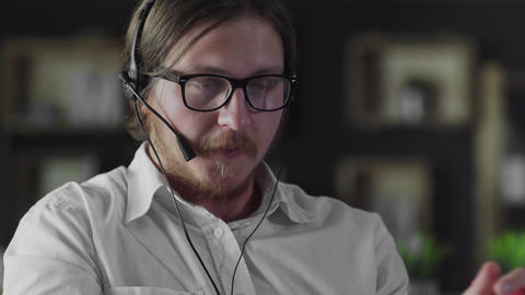Manager in headphones is working at desk in office alone Live Action
