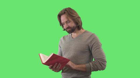 Intelligent Caucasian man closing book in red cover and smiling at camera Live Action