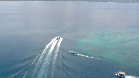 a large boat swims quickly through the blue ocean water with a large footprint Live Action