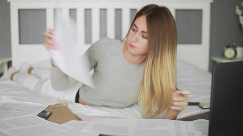 Young woman work at home. Woman lays on the bed and works with documents Live Action