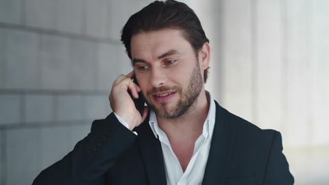 Businessman talking on cellphone with colleague outside. Man celebrating success Live Action