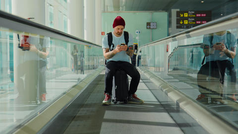 Trendy modern man in empty airport terminal Live Action