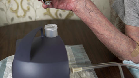 Elderly man hands drop medicine into an inhaler nebulizer Live Action