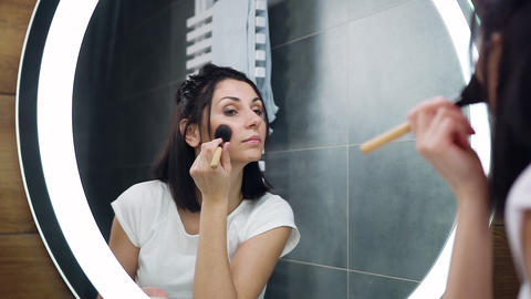 Beautiful concentrated black haired young woman looking into the mirror and Live Action