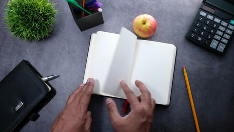 top view of man hand turning a page of a diary Live Action