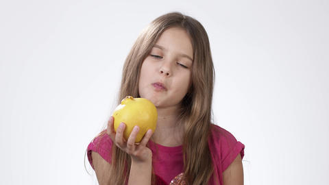 Girl with an Apple. Little girl eats a big yellow apple on a white background Live Action