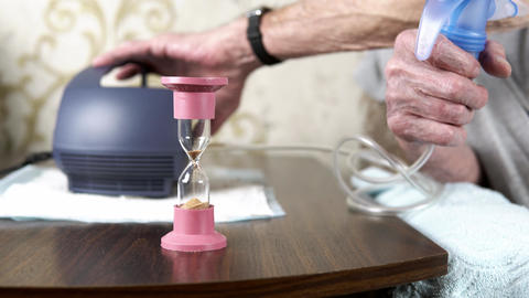 Elderly man hands turn on an inhaler nebulizer in foreground of an hourglass Live Action