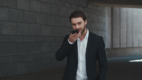 Smiling business man recording voice message on cellphone in modern city Live Action