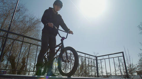 An alone bmx rider in black hoodie on ramps in the skatepark Live Action