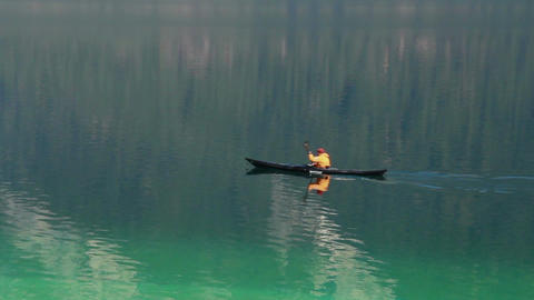 Slow motion shot of man canoeing on beautiful lake, enjoying relax and solitude Footage